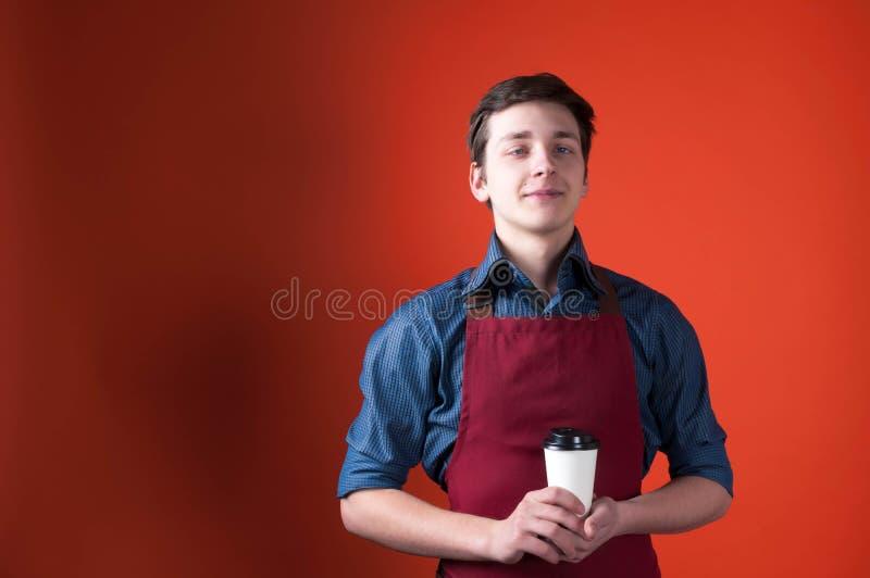 Barista decepcionado con la mueca en el delantal rojo que sostiene la taza de papel con café foto de archivo