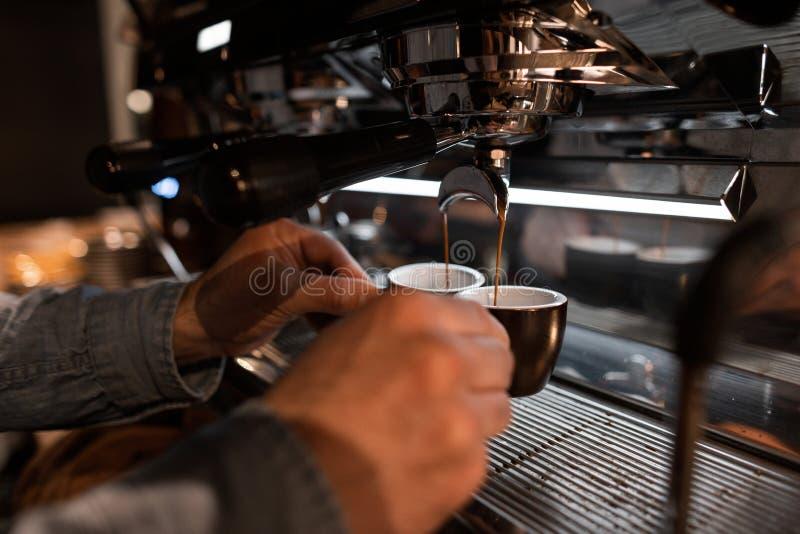 Barista del hombre joven que hace el café express en una máquina del café Las manos masculinas sostienen las tazas negras Descans imagen de archivo