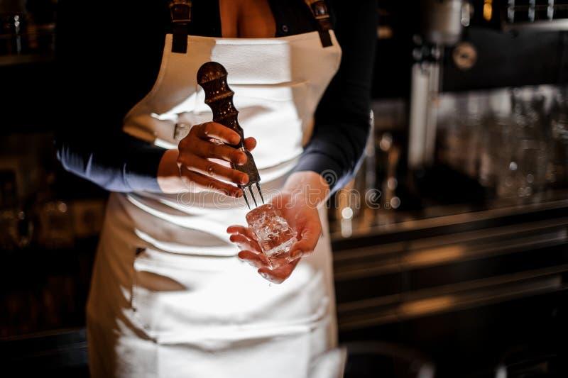 Barista della donna che schiaccia un pezzo di ghiaccio per la fabbricazione del cocktail fotografie stock