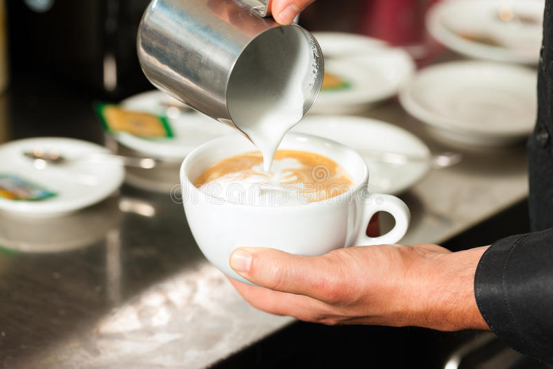 Barista die cappuccino's in zijn coffeeshop maakt stock afbeelding