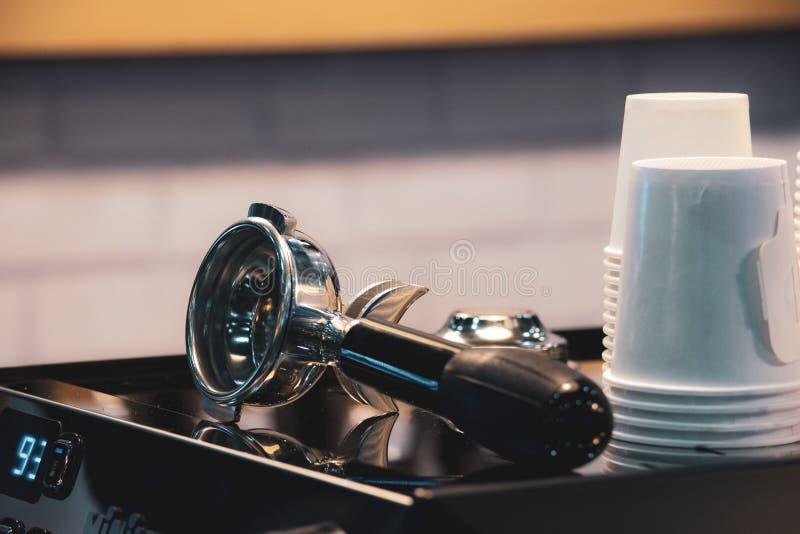 Barista die in een koffiewinkel werken, sluit omhoog van de grondkoffie van baristapersen gebruikend stamper, het Concept van Bar stock fotografie