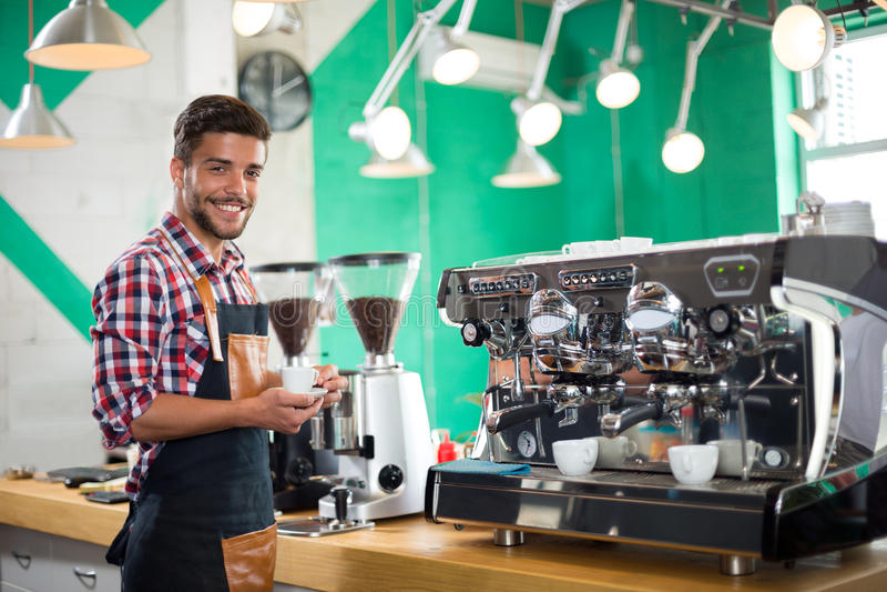 Barista die een kop van koffie aanbieden aan camera in een koffie stock afbeelding