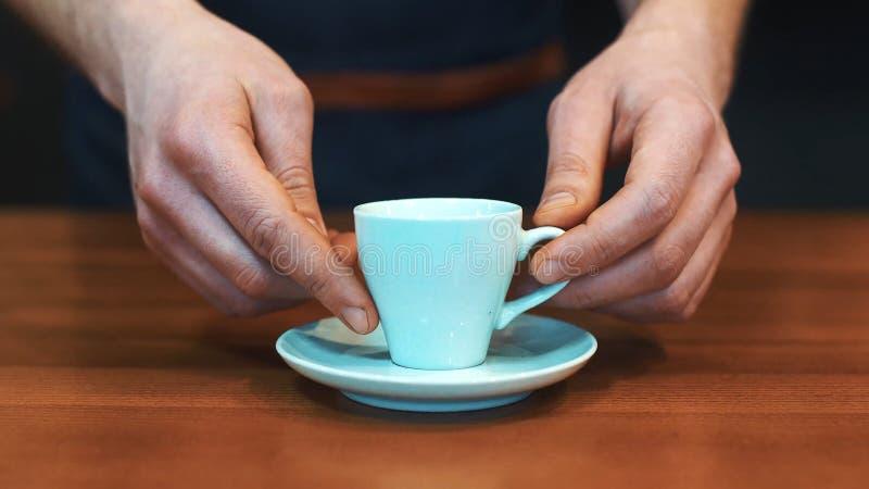 Barista die een kop van koffie dienen aan camera royalty-vrije stock fotografie