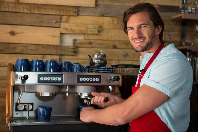 Barista die koffie met machine in koffiewinkel voorbereiden royalty-vrije stock afbeelding