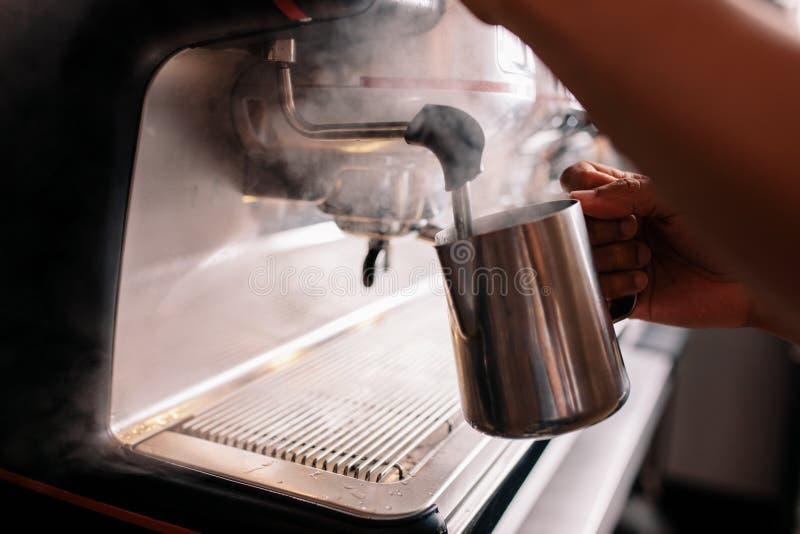 Barista die melk op een koffiemachine stomen bij koffie royalty-vrije stock foto's
