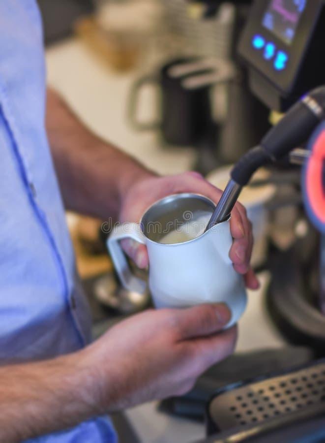 Barista die melk op espressomachine stomen in koffiewinkel stock fotografie