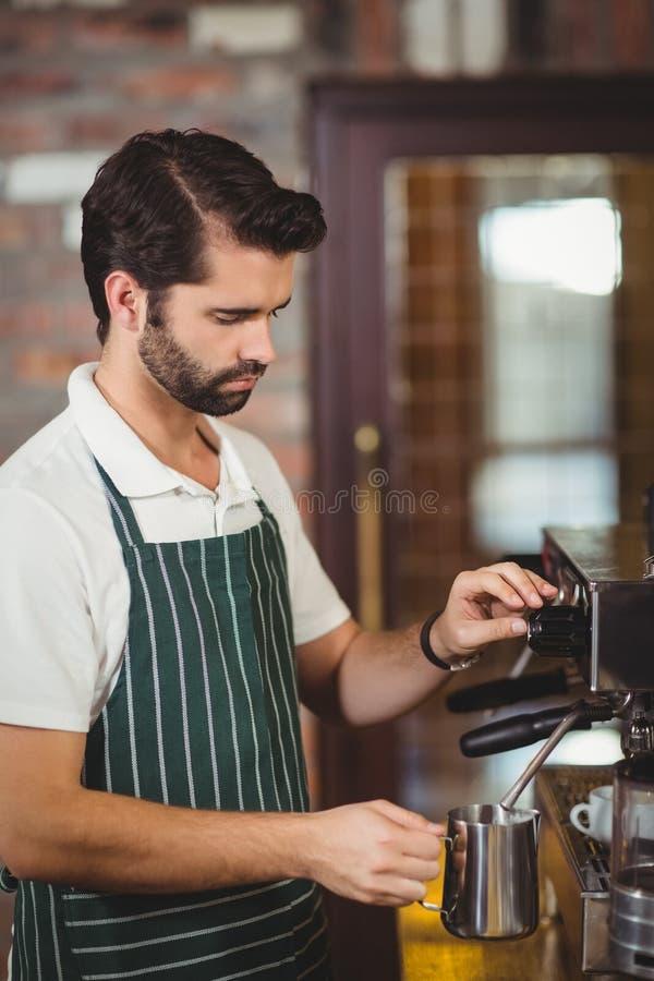Barista die melk stomen bij de koffiemachine stock fotografie
