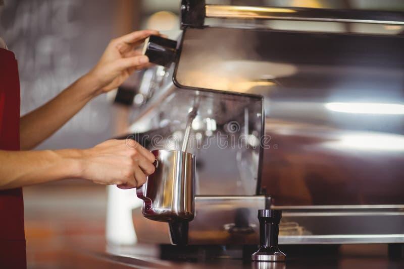 Barista die melk stomen bij de koffiemachine royalty-vrije stock afbeelding