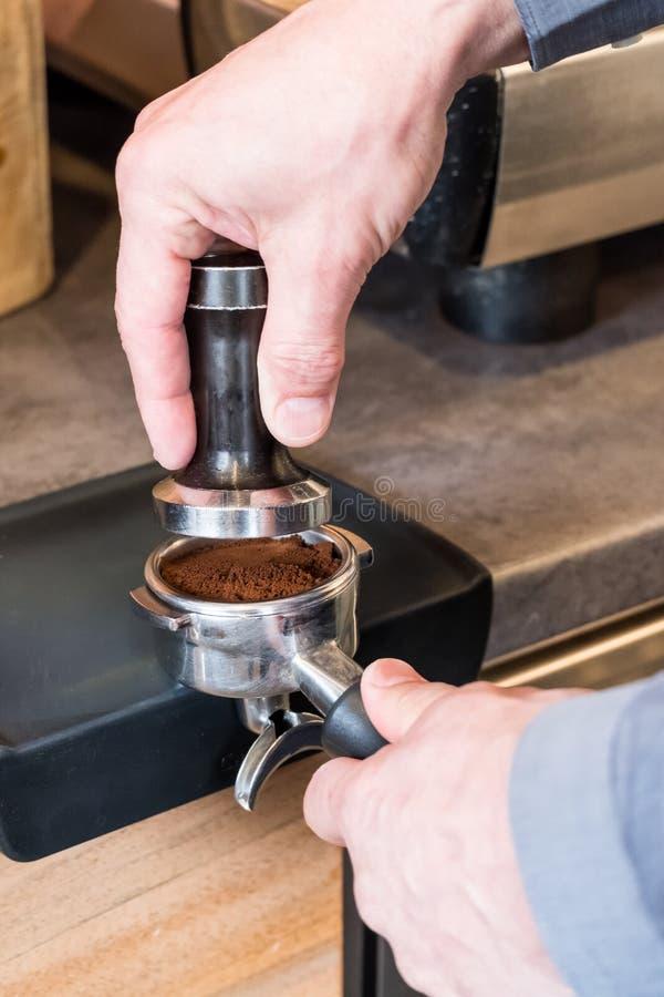 Barista die stamper over koffie plaatsen in portafilter aan het maken espr stock foto's