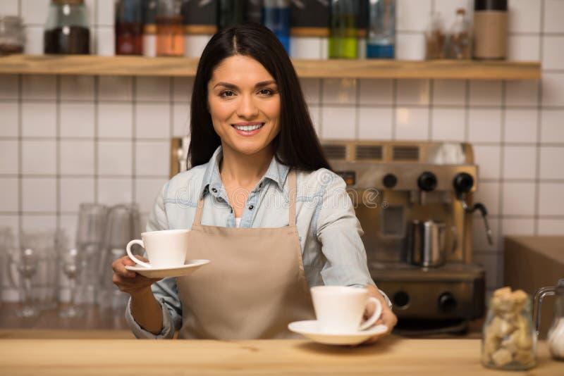 Barista die twee koppen van koffie houden royalty-vrije stock afbeelding
