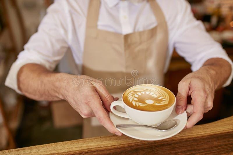 Barista die u een kop van verse koffie geven stock fotografie