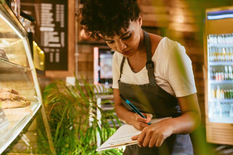 Barista die voorraad in dessertshowcase controleren stock fotografie