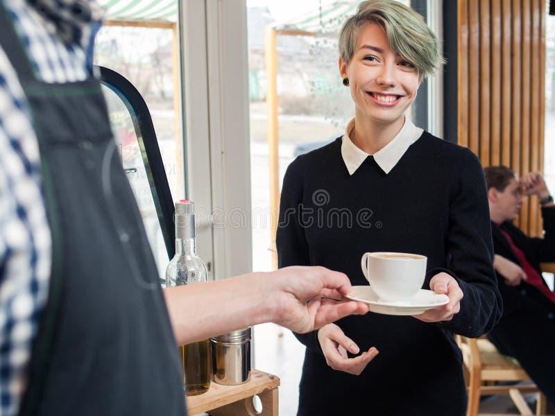 Barista dient de winkel van de het meisjeskoffie van de kopcliënt hipster royalty-vrije stock fotografie