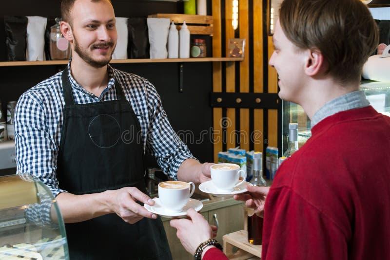 Barista dient de winkel van de de mensenkoffie van de kopcliënt hipster royalty-vrije stock afbeeldingen