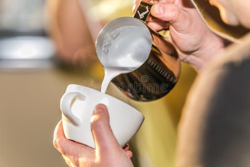 Barista do close up em preparar a espuma de derramamento do leite do cappuccino apropriado em um copo imagem de stock royalty free