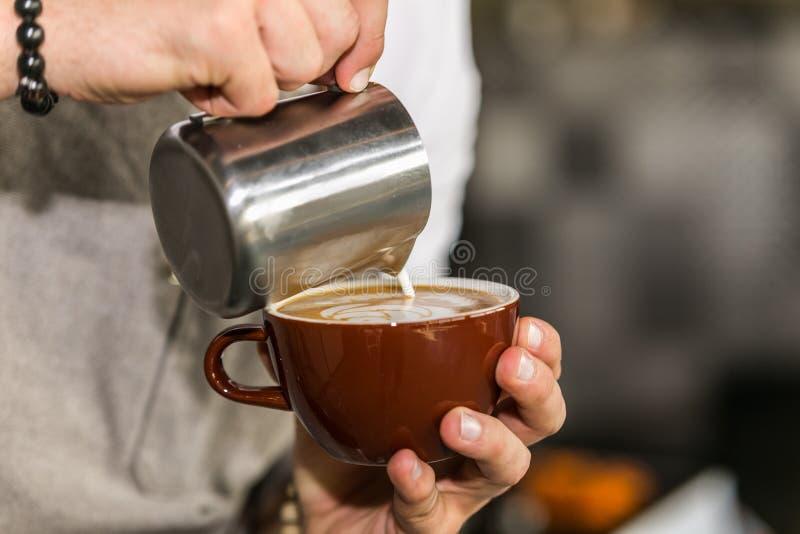 Barista do close up em preparar a espuma de derramamento do leite do cappuccino apropriado em um copo fotos de stock