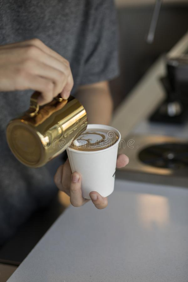 Barista dolewania śmietanka w cappuccino szkło robi pięknej kawowej sztuce zdjęcie stock