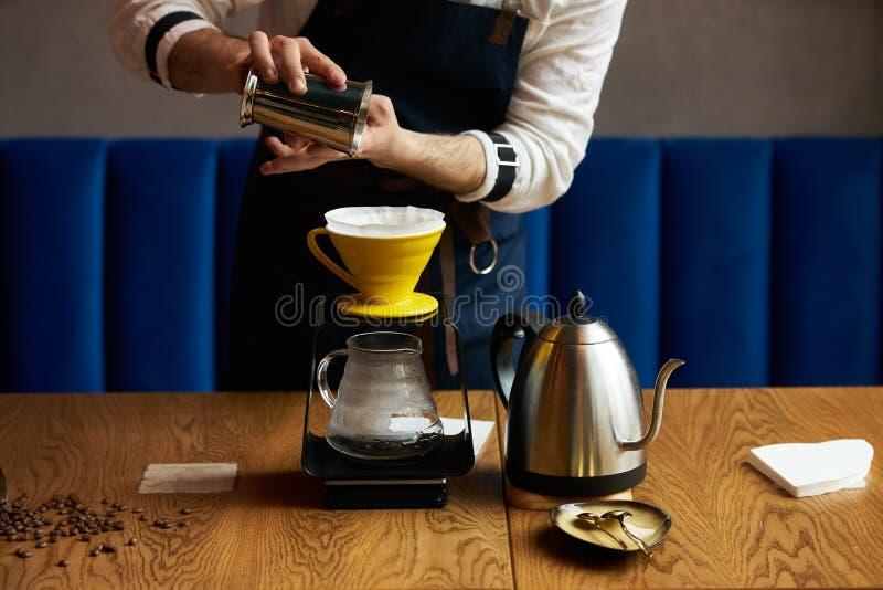 Barista dolewania woda na kawy ziemi z papieru filtrem zdjęcia stock