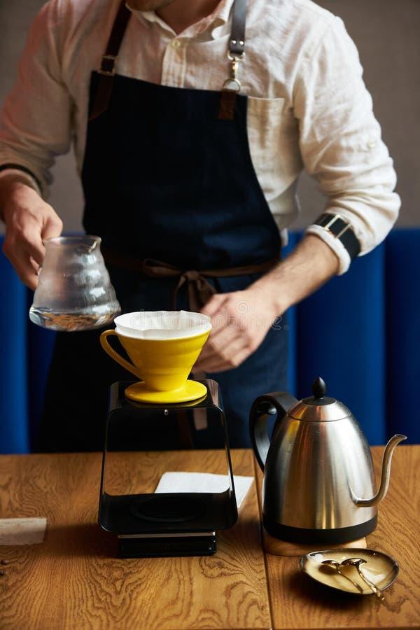 Barista dolewania woda na kawy ziemi z papieru filtrem obrazy stock