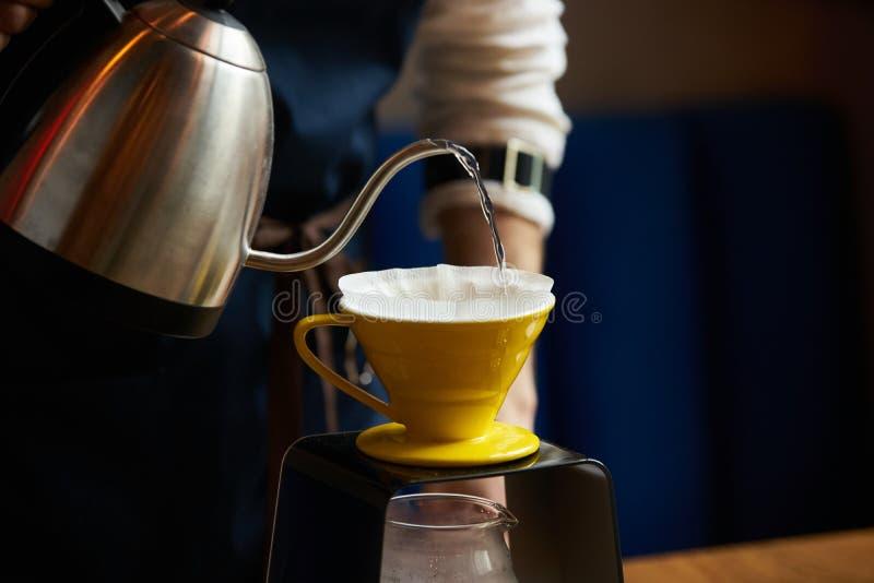 Barista dolewania woda na kawy ziemi z papieru filtrem zdjęcie royalty free