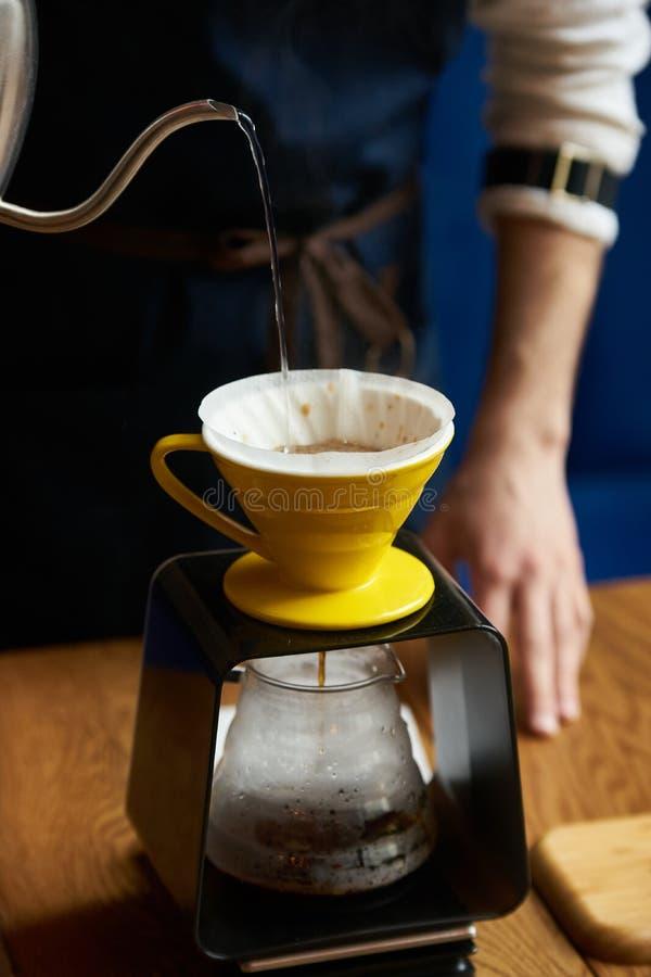 Barista dolewania woda na kawy ziemi z papieru filtrem fotografia royalty free
