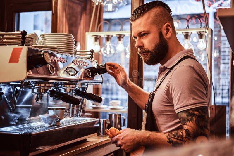 Barista in eenvormig voorbereidend een kop van koffie voor een klant in de koffiewinkel royalty-vrije stock afbeelding