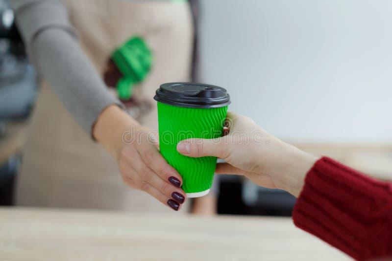 Barista en delantal está dando el café caliente en taza de papel para llevar verde al cliente El café se lleva en la tienda del c fotos de archivo libres de regalías