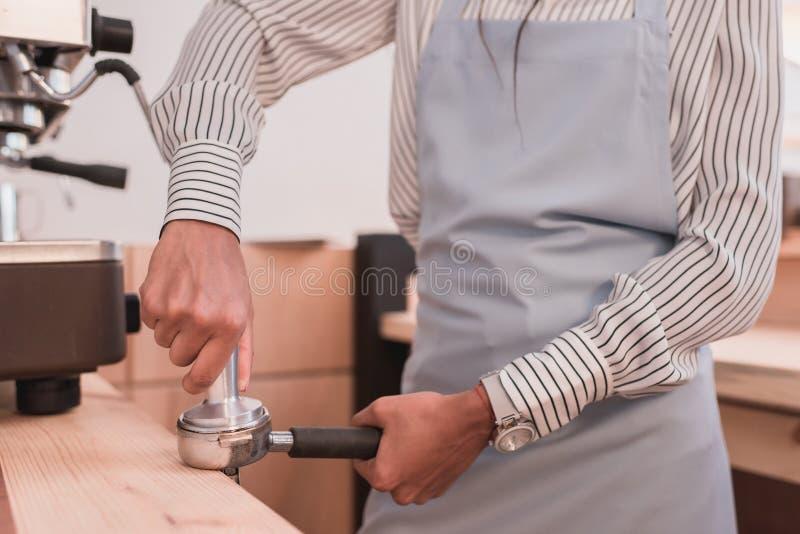 Barista en el café que presiona el café en fotografía de archivo libre de regalías