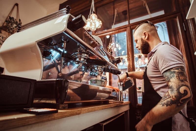 Barista en el delantal que hace un capuchino, una leche de colada en la taza de acero en un restaurante o una cafetería foto de archivo libre de regalías
