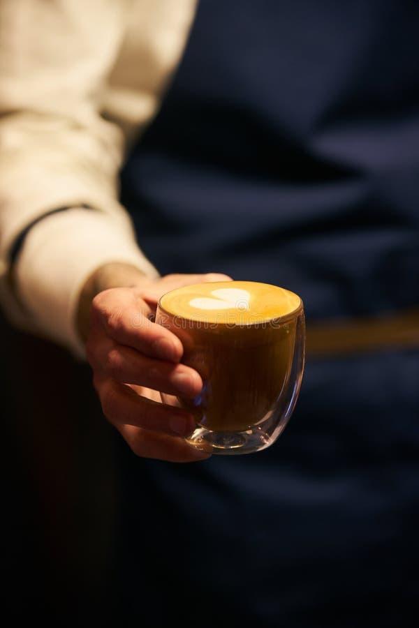 Barista en el uniforme oscuro del delantal que sostiene una taza de café fotos de archivo