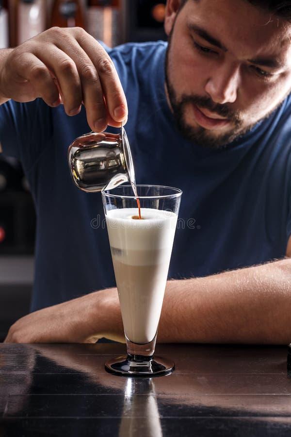 Barista está vertiendo el café en leche fotos de archivo libres de regalías