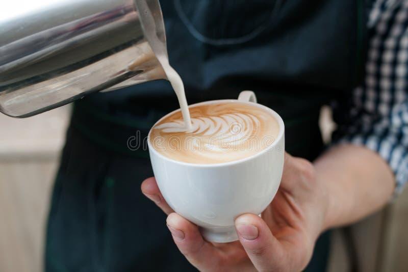 Barista expertis häller mjölkar lattekoppcafeterian arkivbild