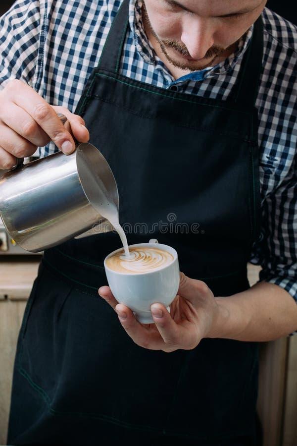 Barista expertis häller mjölkar lattekoppcafeterian royaltyfria bilder