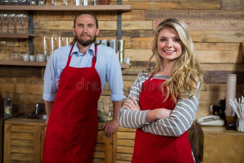 Barista fêmea de sorriso com o colega masculino na cafetaria fotografia de stock