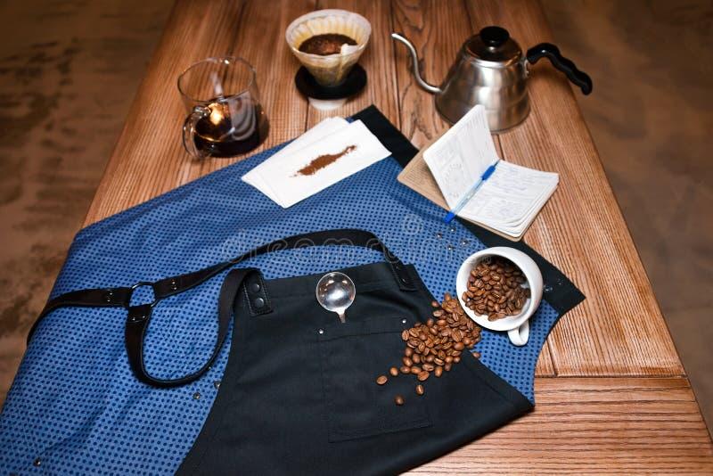 Barista förkläde på tabellen i kafé med olikt material för alternativt brygga för kaffe Produktfotografi förberedelse royaltyfri foto