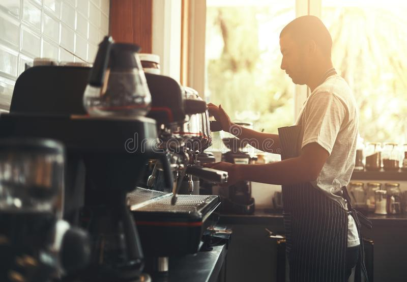 Barista f?rbereder cappuccino i hans coffee shop arkivbilder