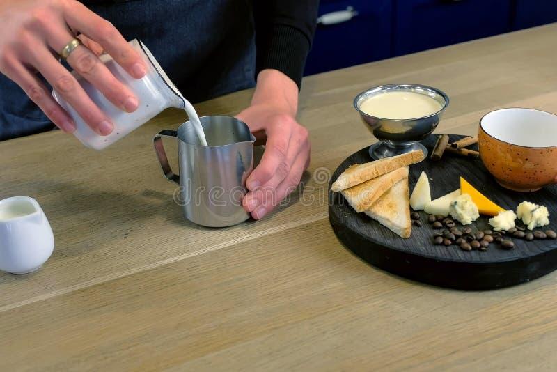 Barista faz o café do queijo, derrama o leite e o creme ao jarro, mãos do close-up fotografia de stock