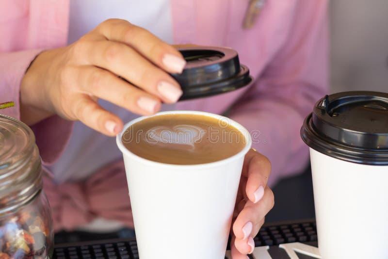 Barista fecha uma caneca com uma tampa de café imagem de stock