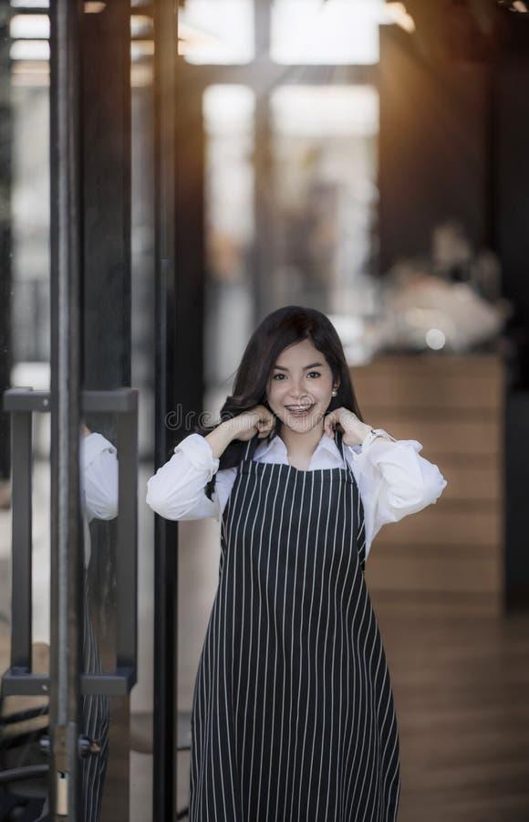 Barista femenino joven que sonríe mientras que se coloca en la puerta imagen de archivo libre de regalías