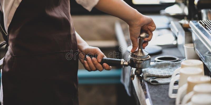 Barista femenino profesional que hace el café foto de archivo