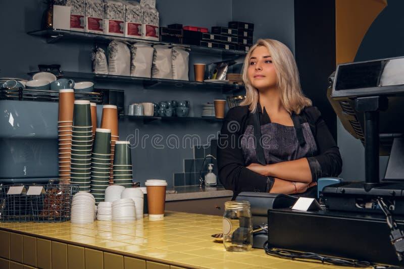 Barista femenino que presenta con los brazos cruzados y que mira de lado en una cafetería o un café imagen de archivo libre de regalías