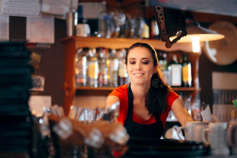 Barista femminile allegro Working Behind il contatore immagine stock