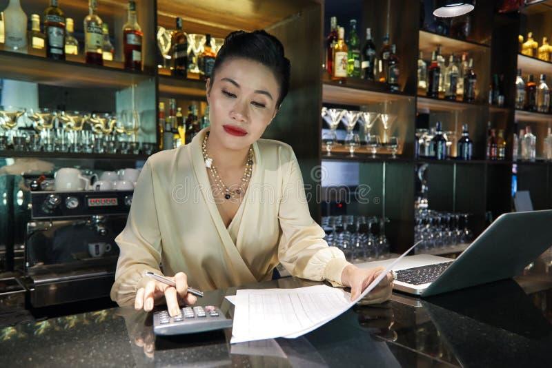 Barista femminile che fa la contabilità commerciale nel luogo di lavoro immagine stock