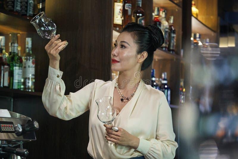 Barista femminile che ispeziona i vetri di vino immagini stock