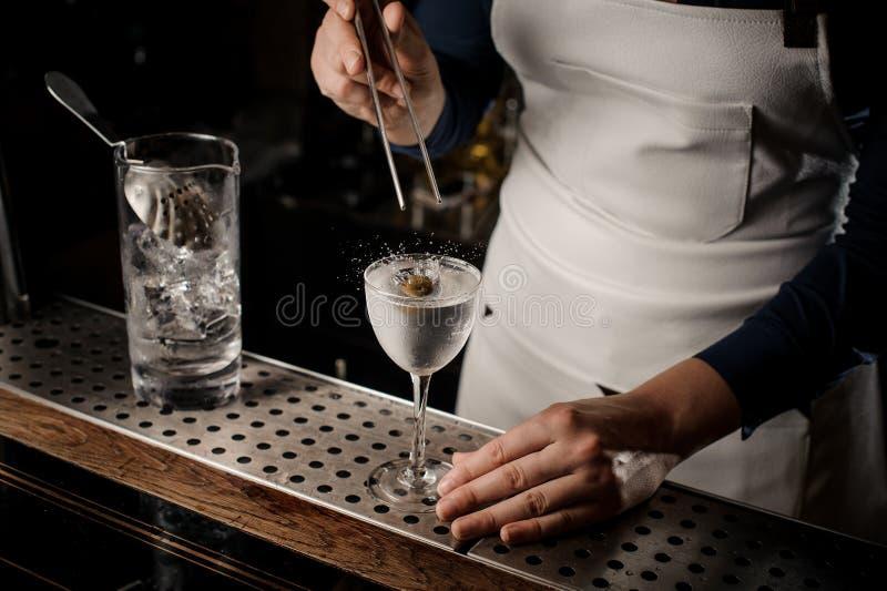 Barista femminile che mette un'oliva in un vetro di cocktail fotografia stock