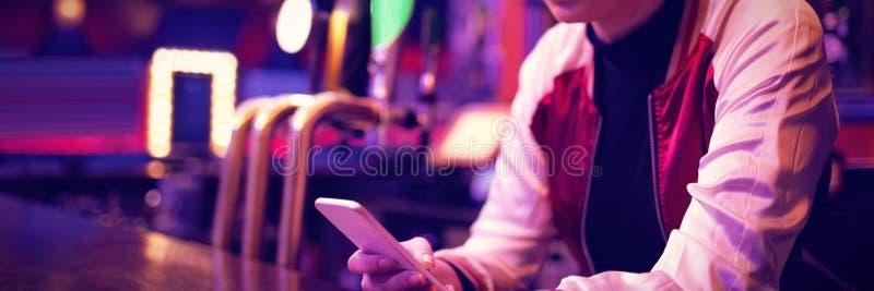 Barista femminile che per mezzo del telefono cellulare al contatore della barra immagini stock