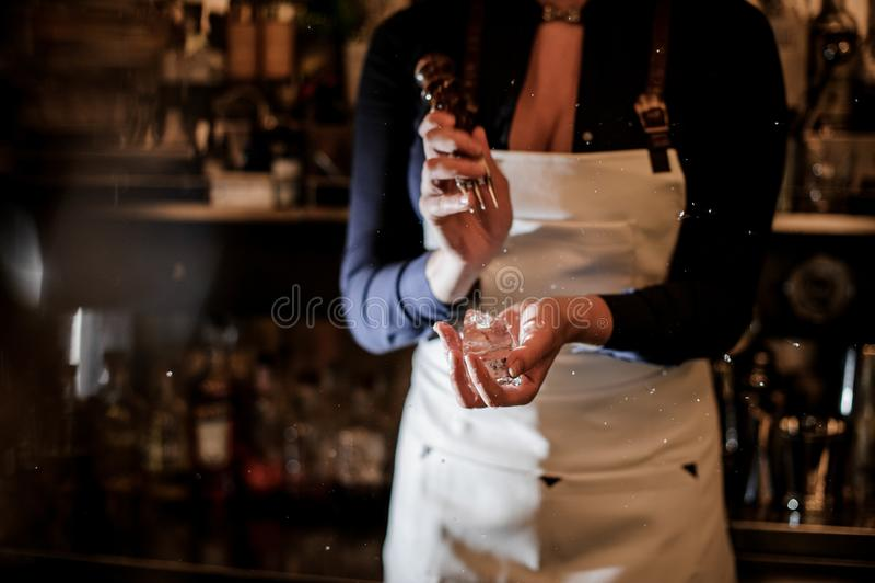 Barista femminile che schiaccia un pezzo di ghiaccio per la fabbricazione del cocktail fotografia stock libera da diritti