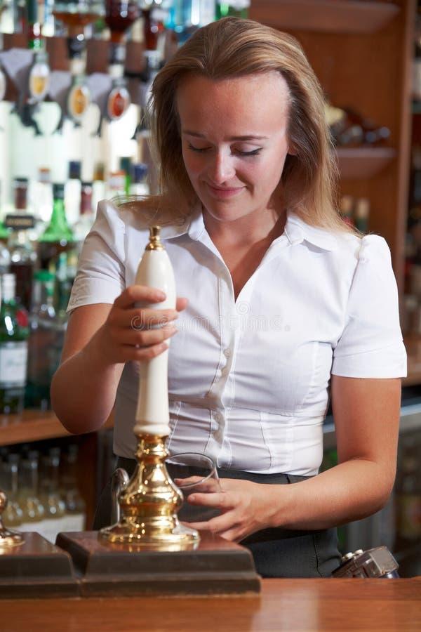 Barista femminile Pouring Beer Behind contro fotografia stock libera da diritti