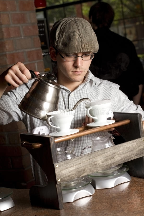 Barista focuses on brewing coffee stock photography