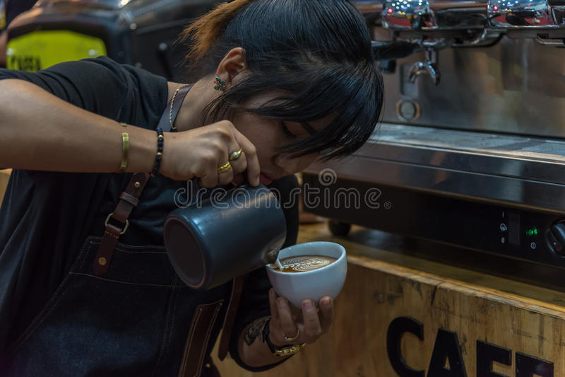 Barista gör hällande lattefradga kaffelattekonst arkivfoto